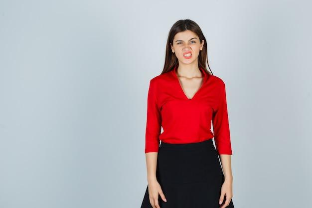 Jonge dame grimassen terwijl poseren in rode blouse, zwarte rok en er zelfverzekerd uitzien