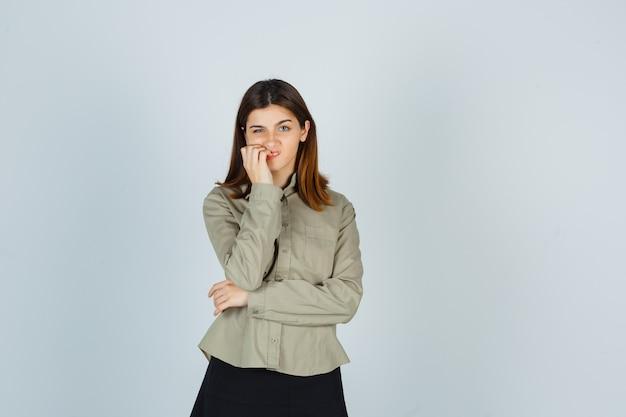 Jonge dame haar nagels bijten in shirt, rok en op zoek attent
