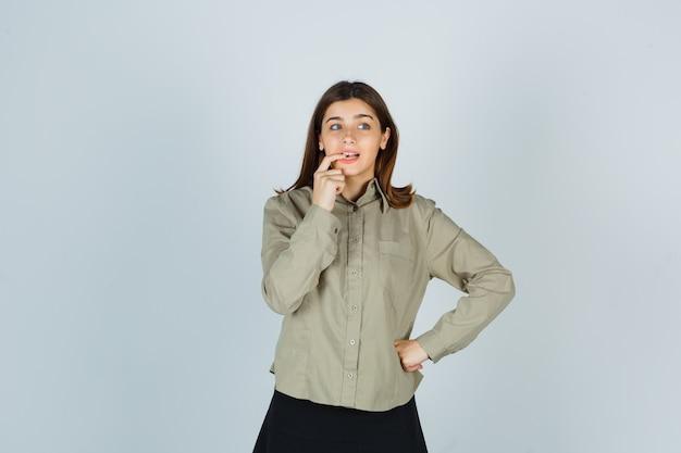 Jonge dame haar nagels bijten in shirt, rok en vergeetachtig op zoek
