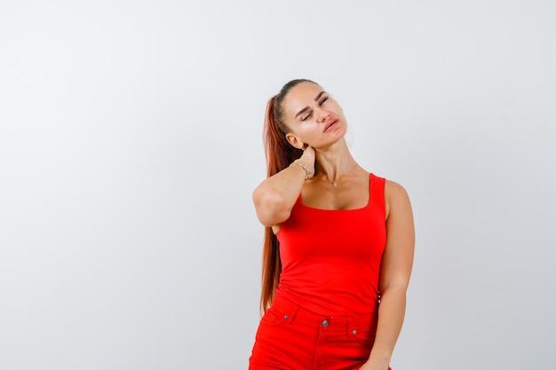 Jonge dame hand achter de nek in rood hemd, rode broek en ziet er moe uit. vooraanzicht.