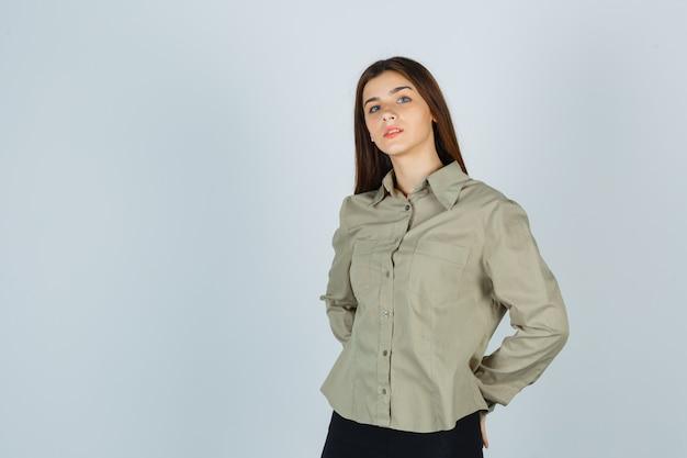 Jonge dame hand in hand achter de rug in shirt, rok en ziet er verstandig uit, vooraanzicht.