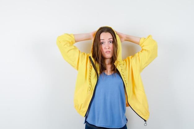Jonge dame hand in hand achter het hoofd in t-shirt, jas en kijkt verbaasd