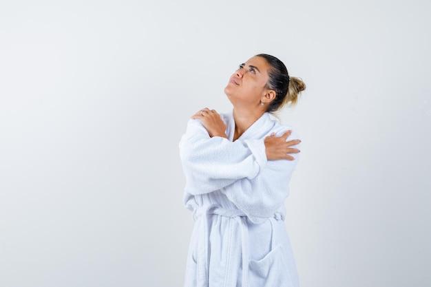 Jonge dame hand in hand gekruist op schouder in badjas en ziet er positief uit
