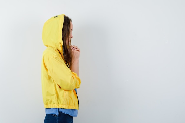 Jonge dame hand in hand gevouwen tijdens het bidden in t-shirt, jas en hoopvol kijken.