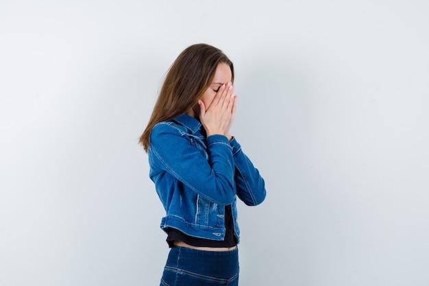 Jonge dame hand in hand in biddend gebaar in blouse en ziet er kalm uit.