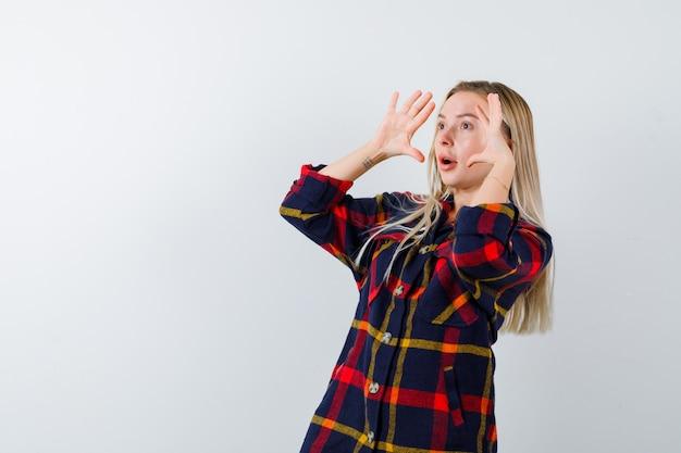 Jonge dame hand in hand in de buurt van gezicht om duidelijk te zien in geruit overhemd en op zoek verbaasd, vooraanzicht.