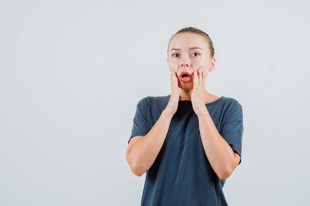 Jonge dame hand in hand in de buurt van mond in grijs t-shirt en verbaasd op zoek