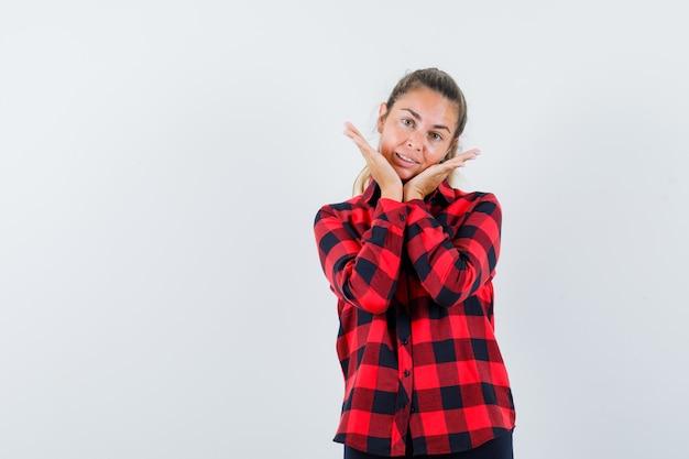 Jonge dame hand in hand onder de kin in geruit overhemd en ziet er schattig uit