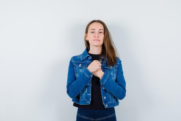 Jonge dame hand in hand op de borst in blouse, jas en ziet er verstandig uit.