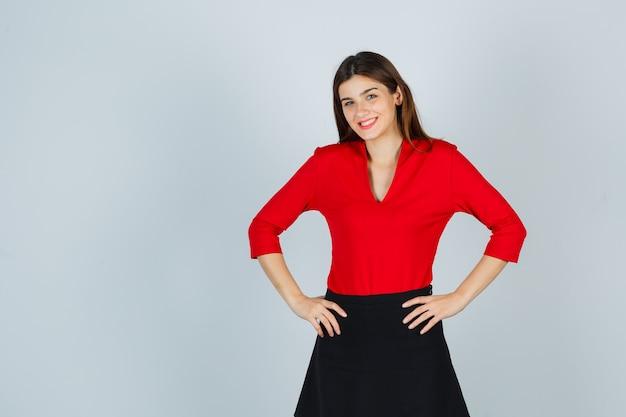 Jonge dame hand in hand op de heupen, glimlachend in rode blouse, zwarte rok en er schattig uit