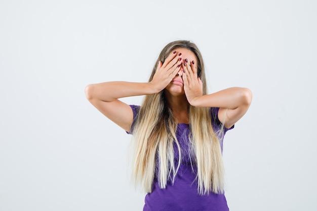 Jonge dame hand in hand op de ogen terwijl ze zich uitstrekt in violet t-shirt en slaperig kijkt. vooraanzicht.
