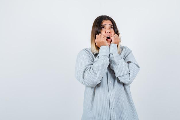 Jonge dame hand in hand op de wangen terwijl ze opkijkt in een oversized shirt en verbijsterd kijkt, vooraanzicht.