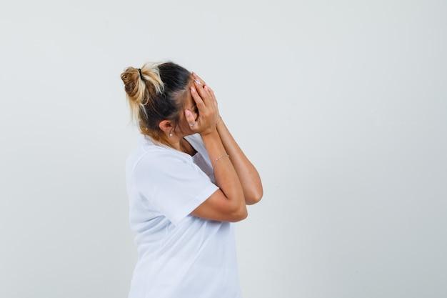 Jonge dame hand in hand op gezicht in t-shirt en beschaamd kijkt