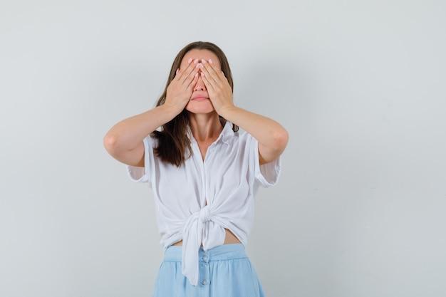 Jonge dame hand in hand op haar ogen in blouse en rok en op zoek verlegen