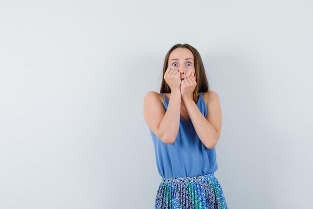 Jonge dame hand in hand op haar wangen in blouse, rok en op zoek bang, vooraanzicht. ruimte voor tekst