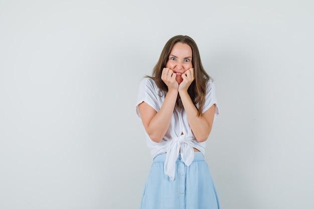 Jonge dame hand in hand op haar wangen in blouse, rok en op zoek stressvol