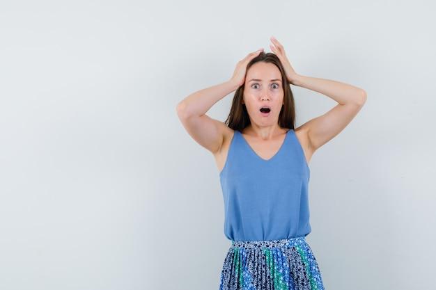 Jonge dame hand in hand op het hoofd in blouse, rok en gealarmeerd op zoek. vooraanzicht.