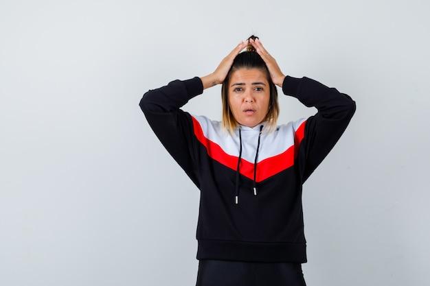 Jonge dame hand in hand op het hoofd in hoodie trui en voorzichtig kijken.