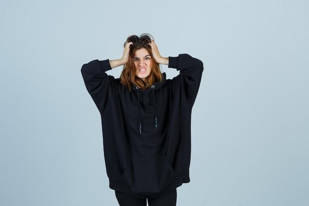 Jonge dame hand in hand op het hoofd in oversized hoodie, broek en op zoek verontrust. vooraanzicht.