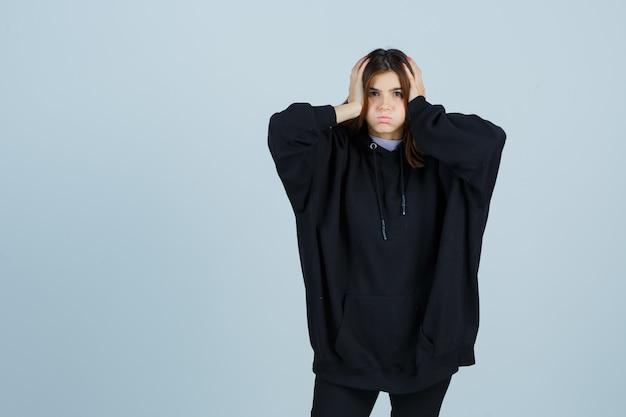 Jonge dame hand in hand op het hoofd in oversized hoodie, broek en ziet er moe, vooraanzicht uit.