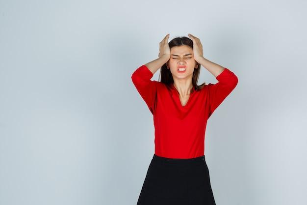 Jonge dame hand in hand op het hoofd in rode blouse, rok en uitgeput op zoek