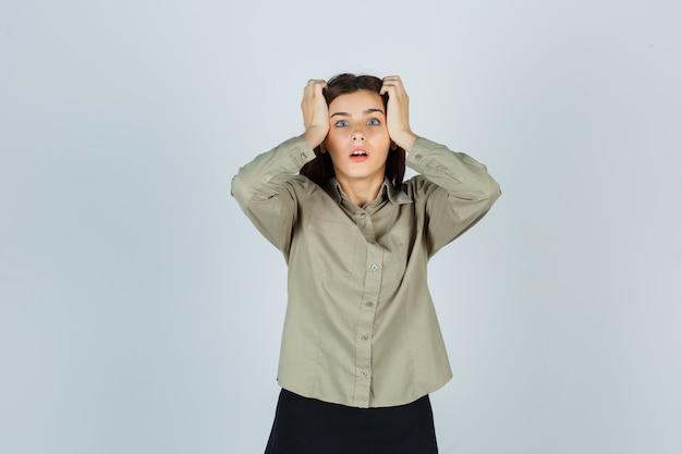 Jonge dame hand in hand op het hoofd in shirt, rok en kijkt geschokt, vooraanzicht.
