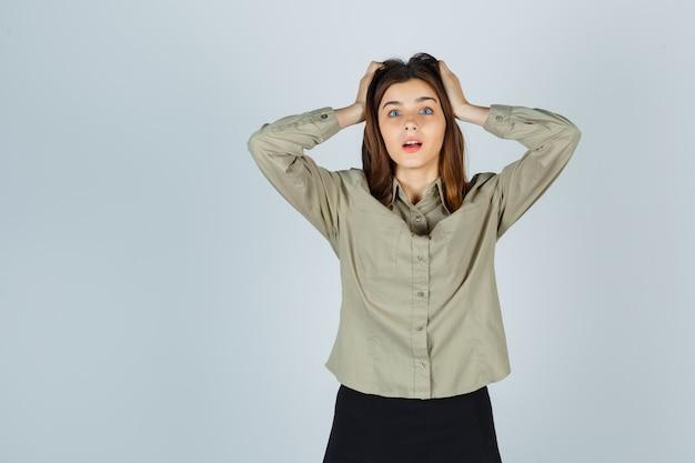 Jonge dame hand in hand op het hoofd in shirt, rok en verbijsterd, vooraanzicht.