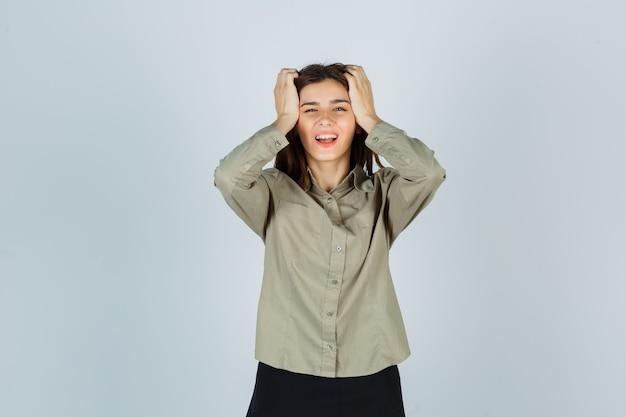Jonge dame hand in hand op het hoofd in shirt, rok en vergeetachtig kijken. vooraanzicht.