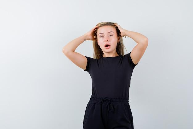 Jonge dame hand in hand op het hoofd in t-shirt, broek en op zoek naar verleidelijk, vooraanzicht.