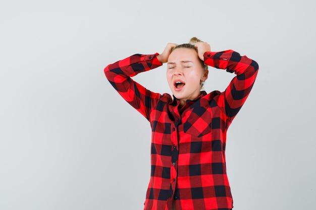 Jonge dame hand in hand op het hoofd terwijl ze schreeuwt in geruit overhemd en gekwetst kijkt