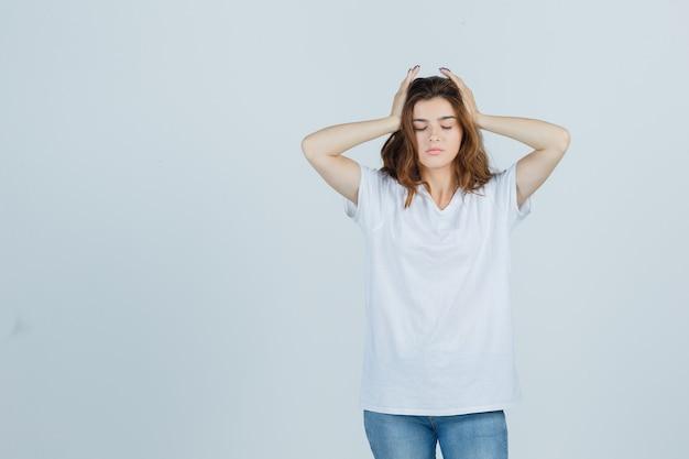 Jonge dame hand in hand op hoofd in t-shirt, spijkerbroek en op zoek moe, vooraanzicht.