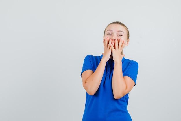 Jonge dame hand in hand op mond in blauw t-shirt en op zoek gelukkig