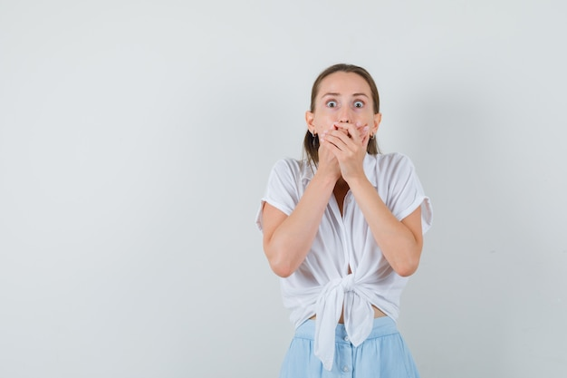 Jonge dame hand in hand op mond in blouse en rok en bang op zoek