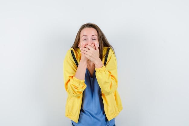 Jonge dame hand in hand op mond in t-shirt en ziet er gelukkig uit, vooraanzicht.