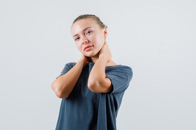 Jonge dame hand in hand op nek in grijs t-shirt en schattig op zoek
