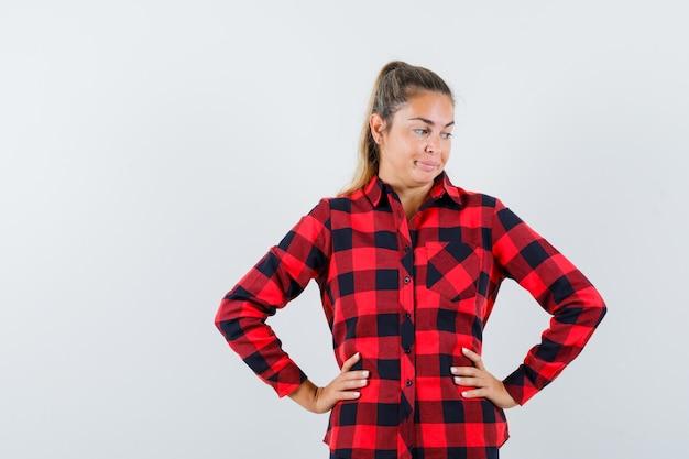 Jonge dame hand in hand op taille in geruit overhemd en wanhopig op zoek
