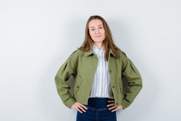 Jonge dame hand in hand op taille in shirt, jas en ziet er aantrekkelijk uit. vooraanzicht.