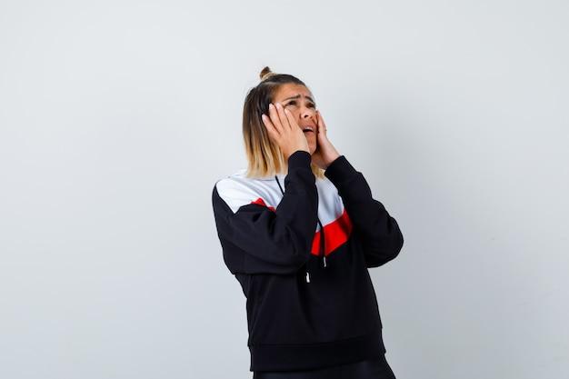 Jonge dame hand in hand op wangen in hoodie trui en bedroefd kijken.