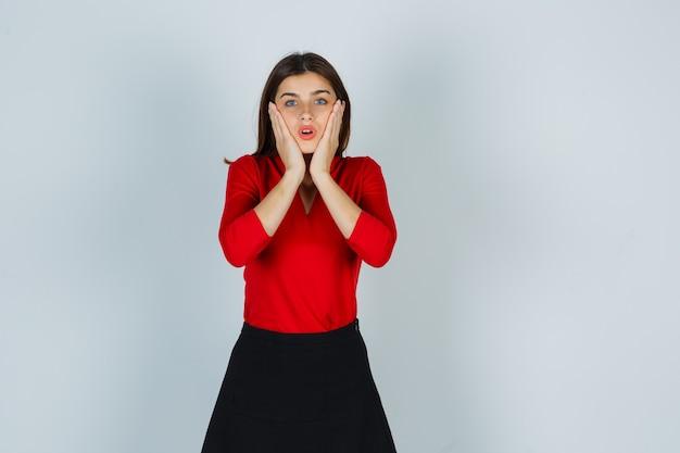 Jonge dame hand in hand op wangen in rode blouse, rok en op zoek verbaasd