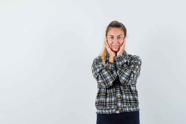 Jonge dame hand in hand op wangen in shirt, korte broek en op zoek schattig. vooraanzicht.
