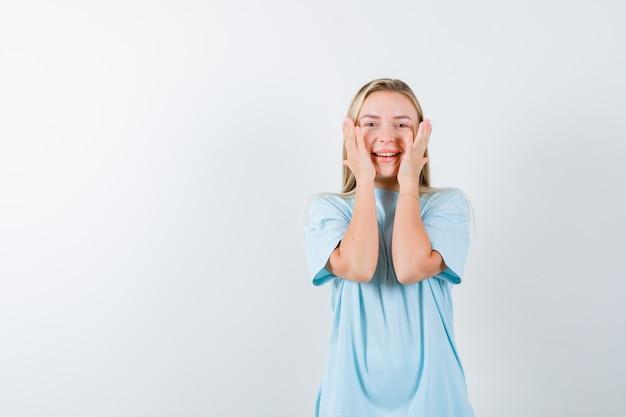 Jonge dame hand in hand op wangen in t-shirt en op zoek gelukkig, vooraanzicht.