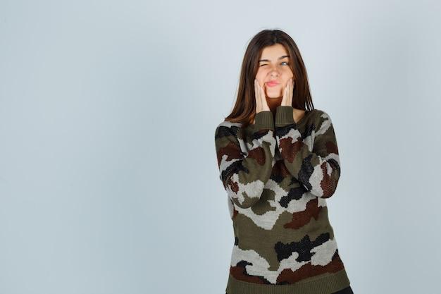 Jonge dame hand in hand op wangen in trui en ontevreden op zoek