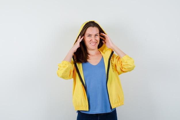 Jonge dame hand in hand terwijl ze fronst in t-shirt, jas en verward kijkt
