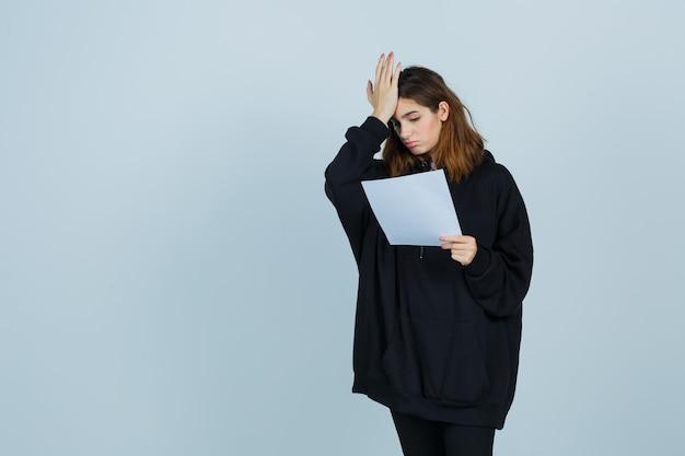 Jonge dame hand op het hoofd terwijl ze papier in een oversized hoodie, broek en vergeetachtig, vooraanzicht houdt.