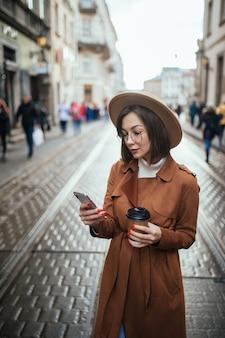 Jonge dame heeft een videocall en drinkt koffie terwijl ze buiten in de stad loopt