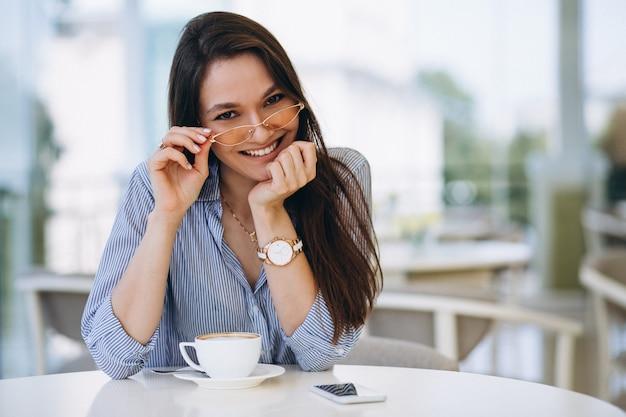 Jonge dame het drinken van thee in een café