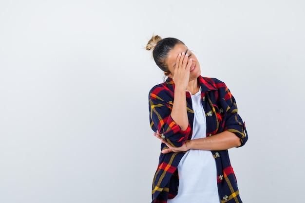 Jonge dame hoofd aan te raken met haar hand in geruit overhemd en op zoek weemoedig