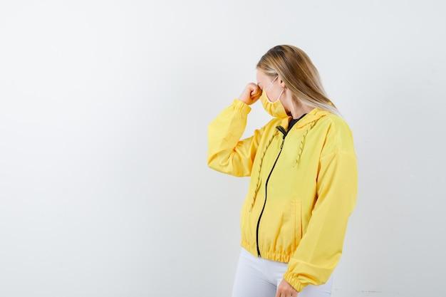 Jonge dame hoofd naar beneden buigen in jas, broek, masker en op zoek depressief, vooraanzicht.