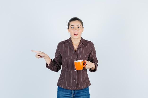 Jonge dame houdt beker vast, wijst naar de zijkant in shirt, spijkerbroek en kijkt verrast, vooraanzicht.