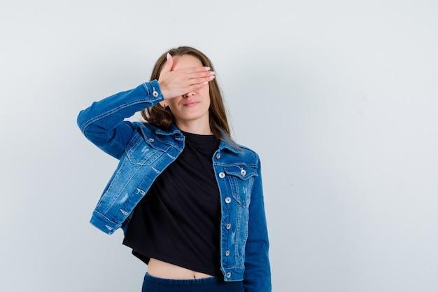 Jonge dame houdt de hand op de ogen in blouse, jas en ziet er positief uit. vooraanzicht.